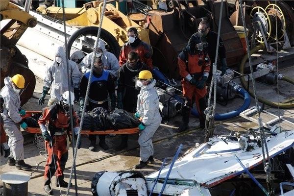 A balesetben elsüllyedt Hableány turistahajó roncsából kiemelt holttestet viszik a Margit hídnál horgonyzó uszályon