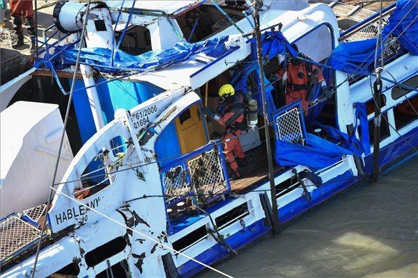 Búvárok a kiemelést követően a víz felszíne felett, holtestek után kutatva átvizsgálják a balesetben elsüllyedt Hableány turistahajó roncsát a Margit hídnál
