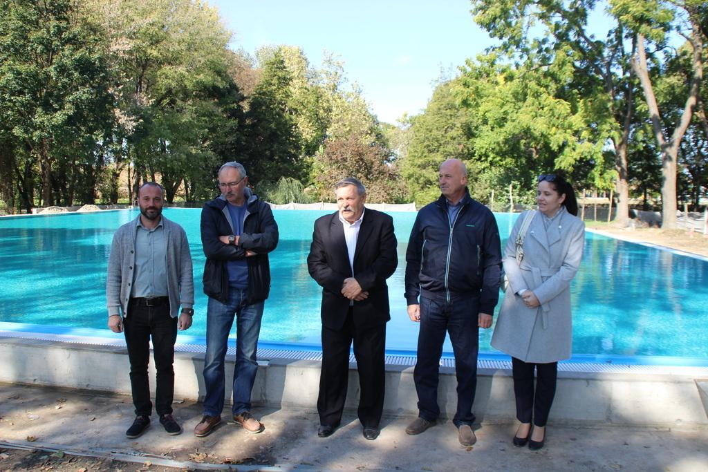 A polgármester (középen) munkatársaival a medencénél