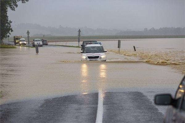 A katasztrófavédelm gépjárműve és egy terepjáró halad a nagy esőzés miatt vízzel elárasztott Csurgót és Gyékényest összekötő úton, a Somogy megyei Porrogszentkirály közelében