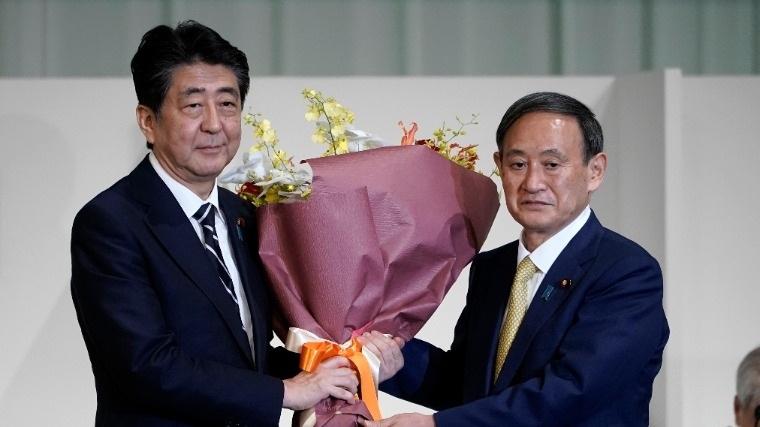 Abe Sindzó japán miniszterelnök virágot nyújt át Szuga Josihide kormányszóvivőnek, miután utóbbi megnyerte a japán kormánypárt, a Liberális Demokrata Párt (LDP) új vezetőjének megválasztására kiírt szavazást